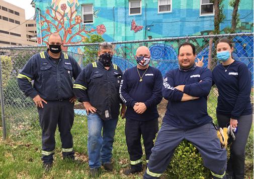 Covanta employees pose at garden