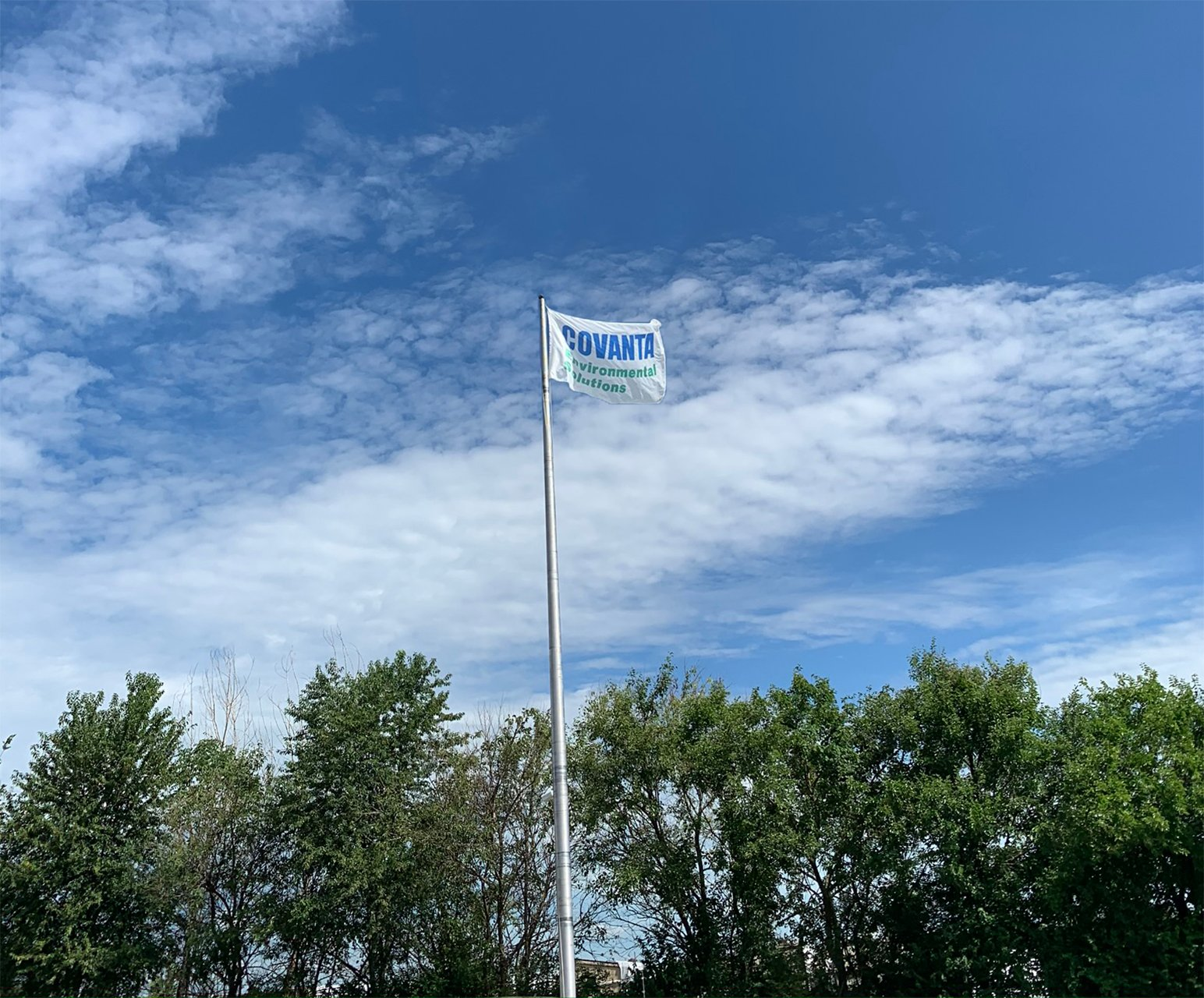 Covanta Environmental Solutions flag waving on blue sky above the tree line