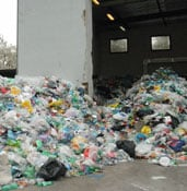 piles of plastic waste outside a garage