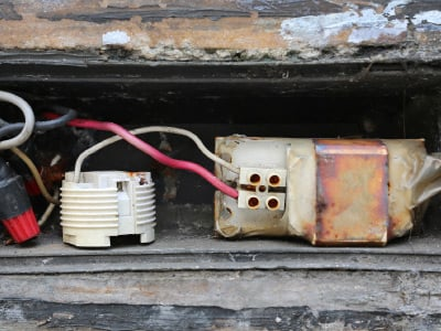An old, electrical ballast lies with exposed wire