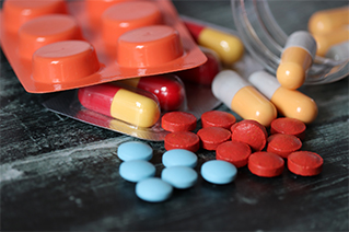 colorful pharmaceuticals spill onto a black table