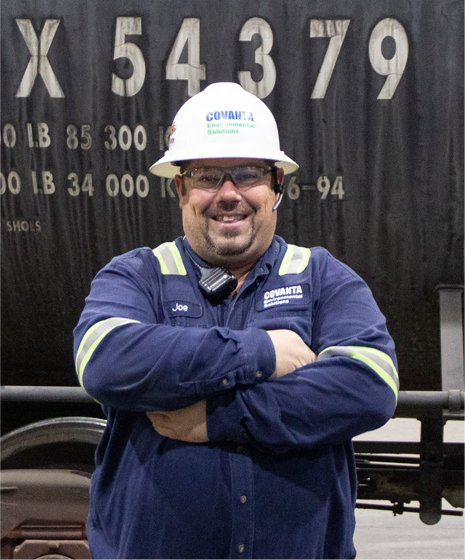 a CES employee smiles with arms crossed in front of a rail car