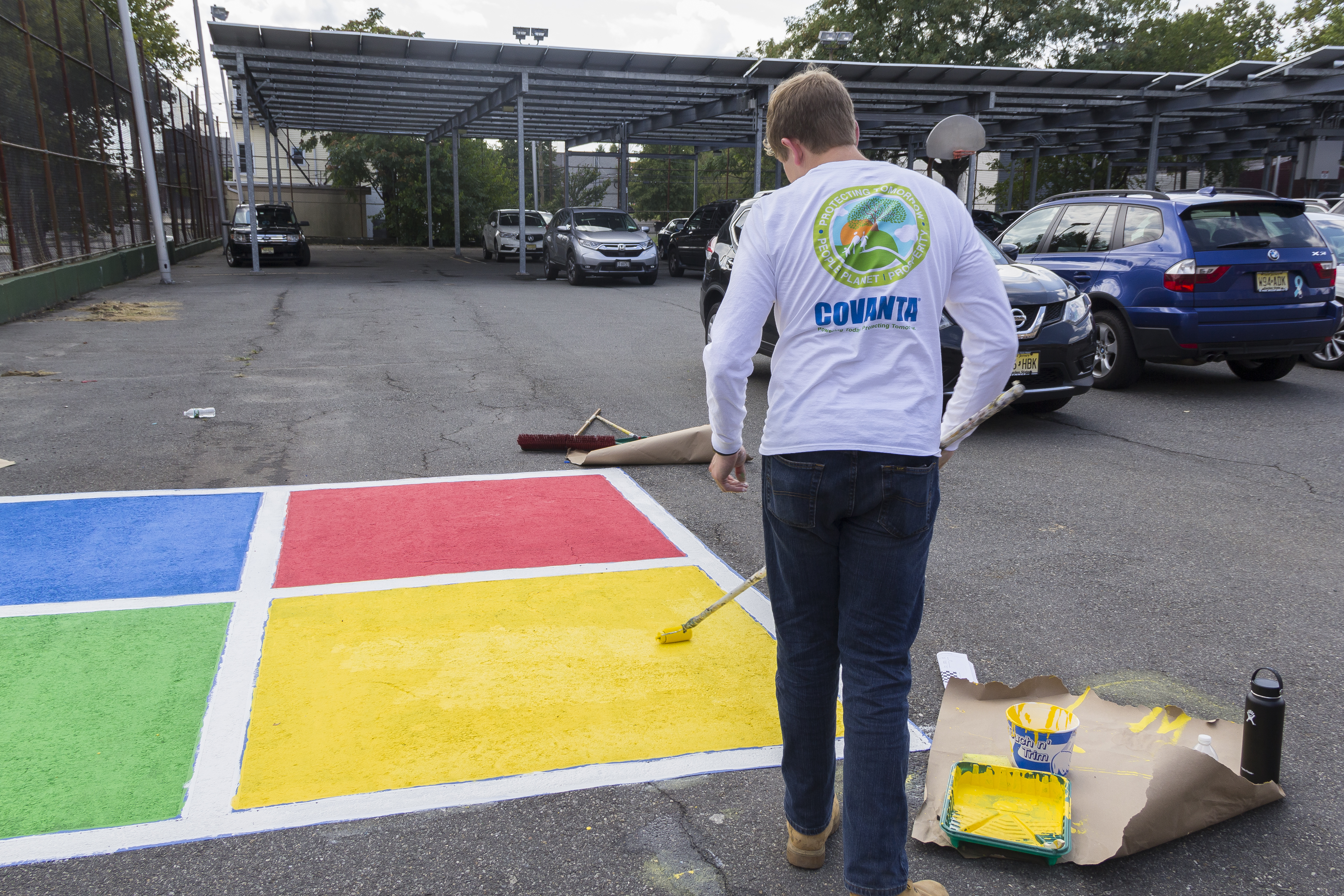 Covanta employee paint a four-square space children at a local school