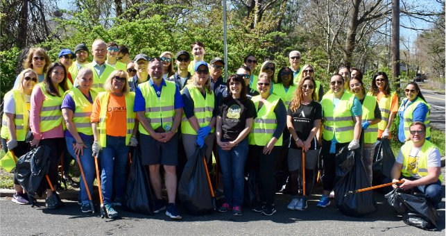 A team of Covanta employees beautifies a neighborhood by cleaning up trash